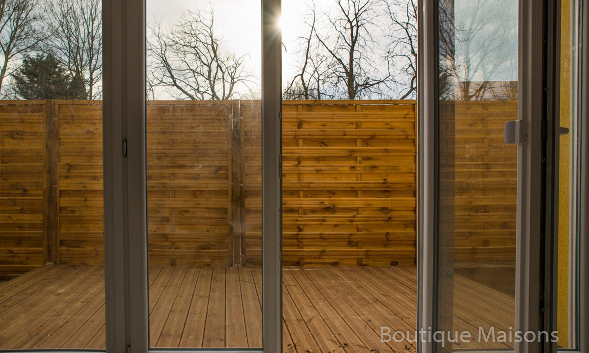 Maison 1 - Sortie vers terrasse salon (decking bois) - lié avec le jardin derrière la maison